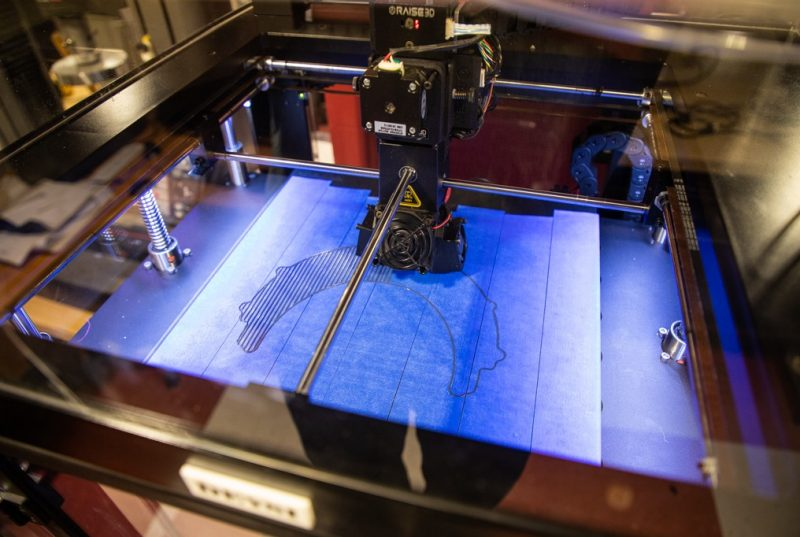 A 3-d printer prints black filament onto a blue build platform underneath.