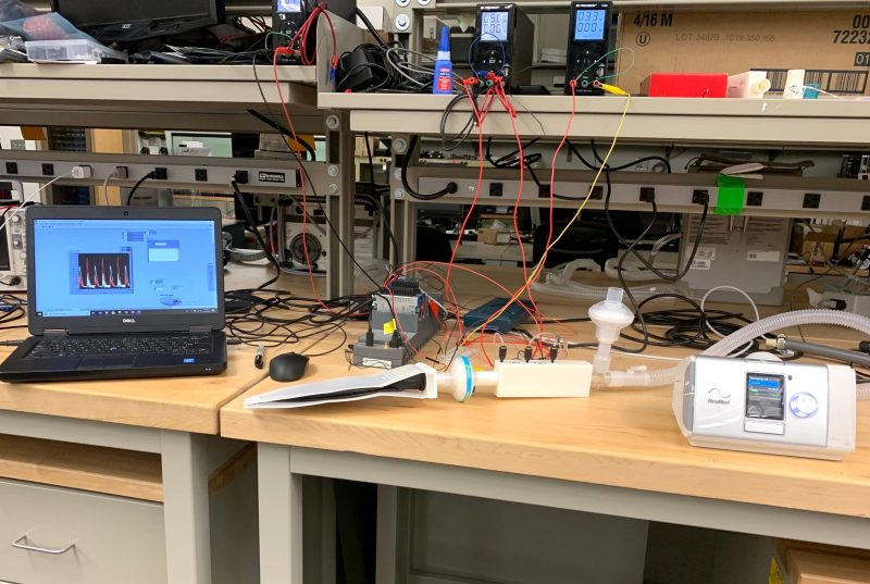 A testing setup in a lab shows a bi-pap machine connected to a test lung.