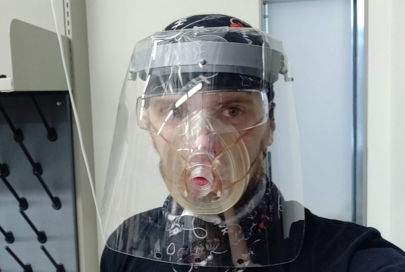 A person in a lab wears a face shield that has a face mask attached.